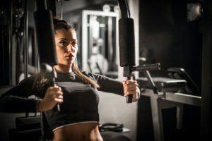 Mulher treinando na estação de musculação