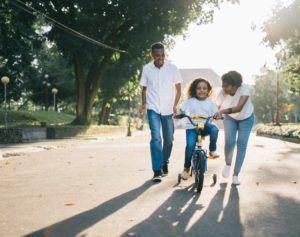 pais ensinando filha a andar de bicicleta